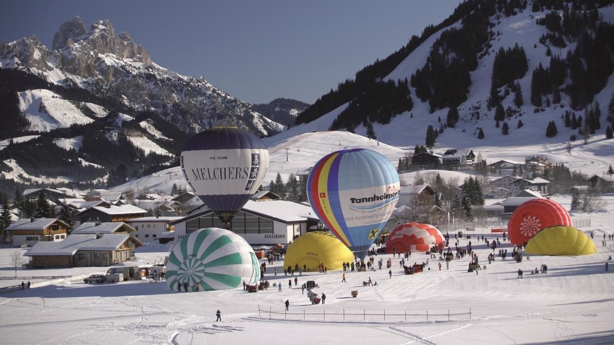 """Es ist eine lange Tradition im Tannheimer Tal: das Internationale Ballonfestival. Jedes Jahr im Jänner zaubern jede Menge Heißluftballons aus aller Welt bunte Farbtupfer an den Himmel. Richtig romantisch wird's beim abendlichen """"Ballonglühen""""., © Tannheimer Tal"""